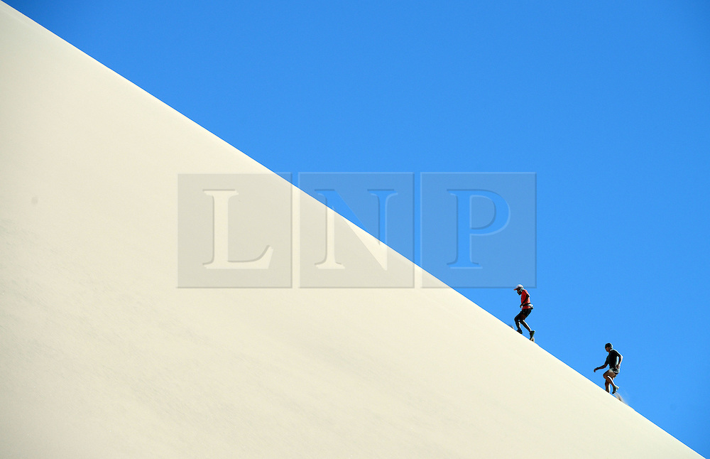 © Licensed to London News Pictures. 14/11/2013.<br /> <br /> The runners go for a training run on a giant sand dune in La Valle de la muerte (The valley of death).<br /> <br /> Inaugural Volcano Marathon, Atacama Desert, Chile. The race took place in the Atacama Desert in Chile, beginning at an altitude of 4,400 metres (14,500 feet) in the vicinity of Lascar Volcano. It was a gruelling affair for many of the competitors who had to encounter some challenging hills and manage the impact of the heat and oxygen deprivation. The average altitude of the entire race was close to 4,000 metres and temperatures reached the mid 20s Celsius, or almost 80 Degrees Farenheit.<br /> <br /> Photo credit : Mike King/LNP<br /> <br /> Further information and link to video here: https://www.dropbox.com/s/0277bepxvo0t8il/Marathon%20copy.txt