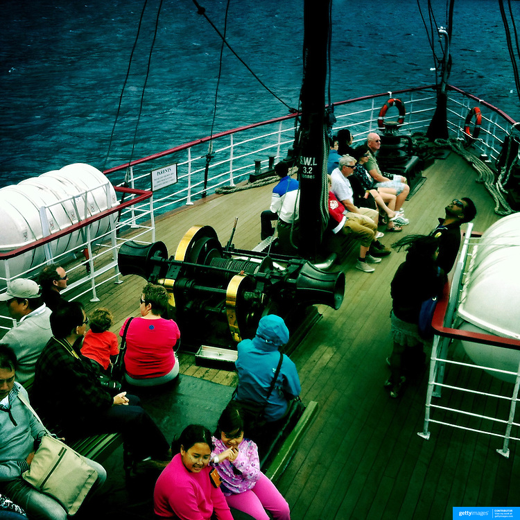Passengers on the fore deck of the TSS Earnslaw, the 100 year old vintage coal fired passenger steam ship which sails on Lake Wakatipu, Queenstown, New Zealand. The popular tourist attraction is celebrating it's centenary year with celebrations planned for October 2012.  Queenstown, Central Otago, New Zealand. 29th February 2012. Photo Tim Clayton