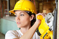 Female construction worker cutting wood with a power saw while looking away