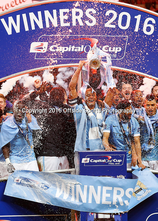 28 February 2016 - The Capital One Cup Final - Liverpool v Manchester City - Vincent Kompany of Manchester City lifts the trophy alongside his team mates - Photo: Marc Atkins / Offside.