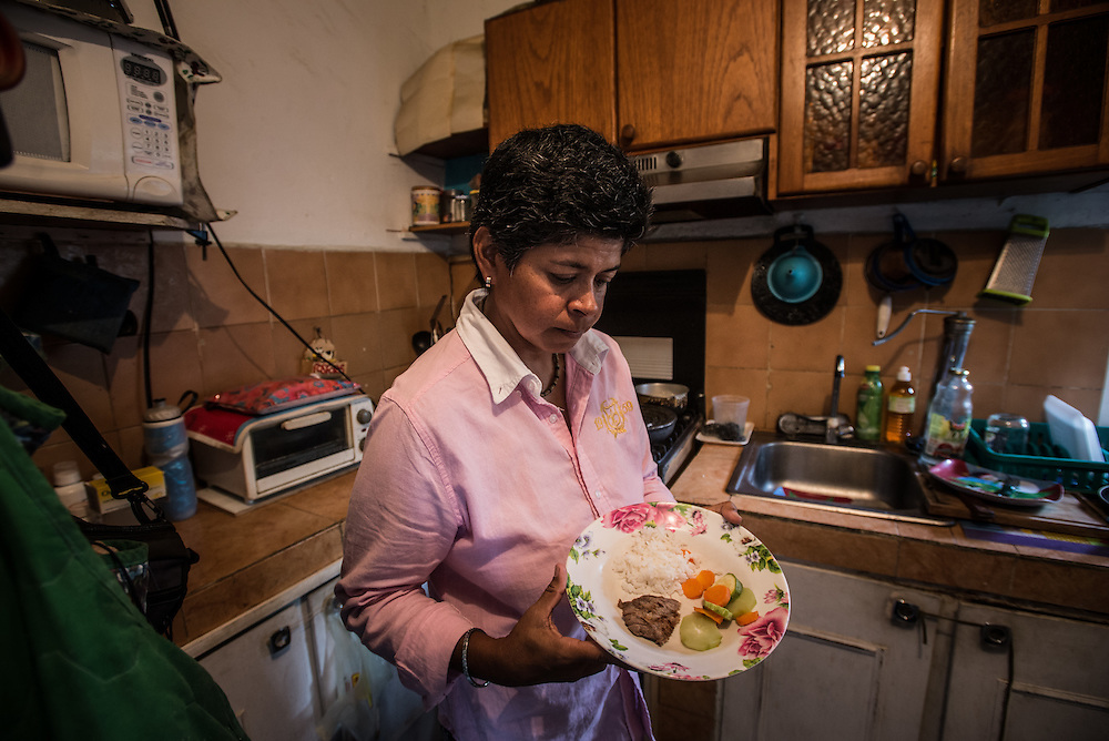 "CARACAS, VENEZUELA - MAY 30, 2016: Vanessa Furtado Fonseca, 45, shows journalists the only meager meal that she will eat that day.  Vanessa lives with her mother, Lucila Fonseca, 65, at their home in a slum in Caracas. Both women are currently suffering from advanced stages of cancer, made worse by the economic crisis because they cannot find nor afford all of the food and medicines that they each require.  Vanessa has a brain tumor that doctors at the free, public hospital cannot treat because of shortages of medicine, and the surgical equipment needed is broken. Doctors at a local private hospital said they can operate to cure her, but that the operation costs $4,000. Vanessa works as a swim instructor, with a monthly salary that is now only worth $24 because of skyrocketing inflation. The insurance plan from her employer ran out months ago, and Vanessa said there is no way she will be able to earn $4,000 dollars in time to save her life.  Doctors have estimated she will only live for three more months without treatment. ""I will die because I am poor,"" she said. In order to stretch her salary far enough to pay for her mother's medical treatments, and for each of them to eat, Vanessa has stopped eating, except for one very small meal, carefully rationed out, each day. She has not told her mother that the doctors said she will die so soon - instead she continues to care for her, trying her best to make the time they have left together happy. PHOTO: Meridith Kohut for The New York Times"