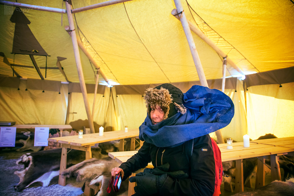 Bundled up woman in warming tent in Svalbard, Norway