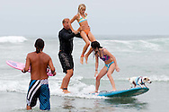 Surfers perform stunts while their canine compatriot hangs ten on the front of the board during the Surf Dog Surf-a-thon in Del Mar.