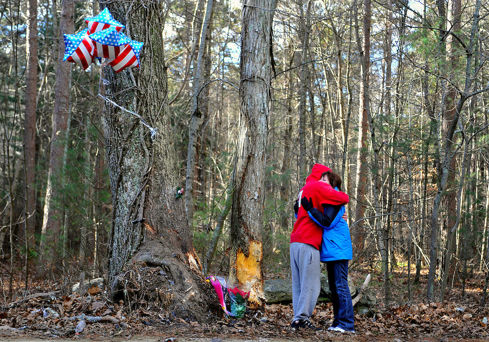 Friend of victims, Bryan Plecan, left, embraces Laura Marsh, of Griswold, a mother who lost her teenage son in an accident four months earlier, at the scene of the crash where four teens were killed in a single-vehicle accident in Griswold, Conn., Wednesday, Dec. 8, 2010.  (AP Photo/Jessica Hill)