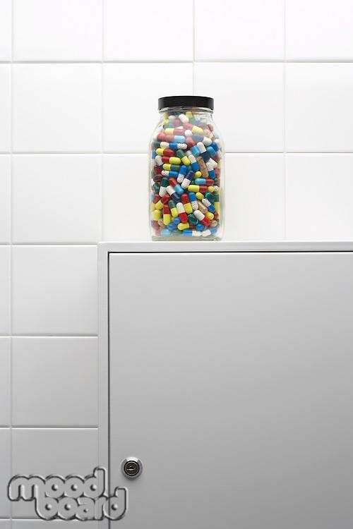 Jar of pills on bathroom cabinet