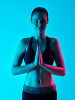 one caucasian woman zen portrait namaste salte yoga  in silhouette studio isolated on blue background