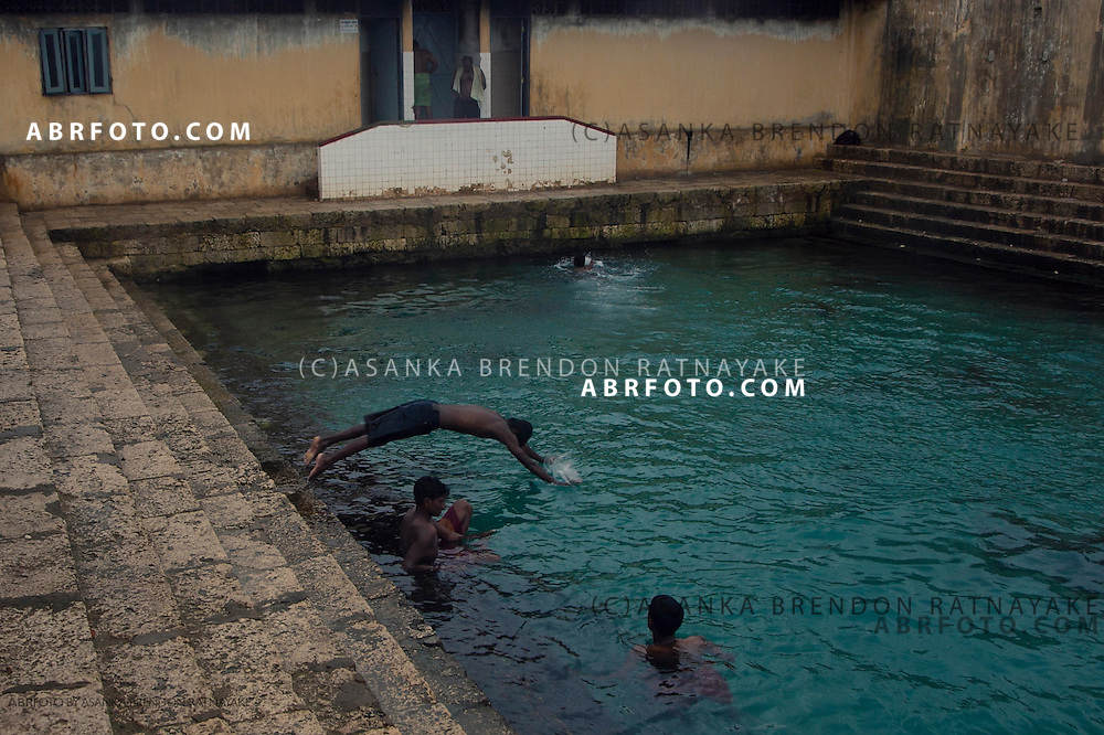 Men swimming in the a mineral water spring called Keerimalai Springs reputed for its curative properties.