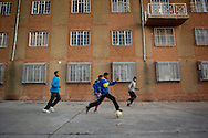 MANENBERG, SOUTH AFRICA - SEPTEMBER 12: Children play with a deflated soccer ball in the parking lot of the Manenberg People Center on September 12, 2013 in Manenberg, a township of Cape Town, South Africa. A gang related shooting occurred a week prior across the street from the Manenberg People Center, which houses various non profit organizations working in the community. Photo by Ann Hermes/The Christian Science Monitor
