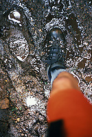 Detail view looking down at the boot of a man hiker crossing through a muddy area of the trail<br />