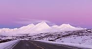 Lenticular clouds at the mountain tops stand in relief against the Belt of Venus at sunrise in Tatshenini-Alsek Provincial Park in British Columbia, Canada. Winter.