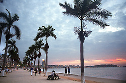 People walk along the main promenade in the capital of Luanda in Angola at dusk in this file photo.  President Jose Eduardo dos Santos, who has led Angola since 1979, said he would not run in presidential elections planned for next year.  Angola's brutal 26 year-civil war has displaced around two million people - about a sixth of the population - and 200 die each day according to United Nations estimates. .(Photo by Ami Vitale)