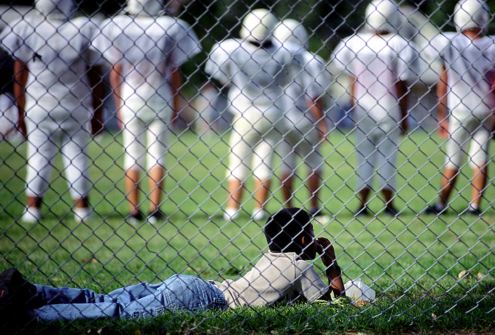 Boy watches middle school football practice while enjoying a sack of popcorn