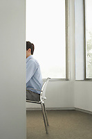 Businessman sitting on chair in office side view obscured face