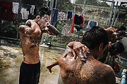 Bangkok  March 2014, inmates and Muay Thai (kickboxing) fighters, washing after a training session at the Klong Prem high-security prison. Klong-prem Central Prison, or generally called Lad-yao prison, is a high-security prison in Bangkok, taking in custody of male offenders whose sentence term is not over 25 years. With its general capacity to incarcerate offenders (5000+), the prison currently takes in custody of both Thai and foreign nationals. <br /> The inmates is part of a program that pits prisoners against foreign Muay Thai fighters or others inmates for a chance of reduced sentencing or early release. In 2012 an Estonian entrepreneur, in conjunction with Thailand's Department of Corrections, began a series of bouts arranged between Thai prisoners and Western Muay Thai fighters under the banner 'Prison Fight'. For the prisoners a victory holds the potential of time off their sentence while the Westerners fight for a small purse and personal ambition. Since the launch of 'prison fight' a number of prisons have adopted the idea, encouraging prisoners to take up boxing to fight drug abuse and to give them a purpose while incarcerated.