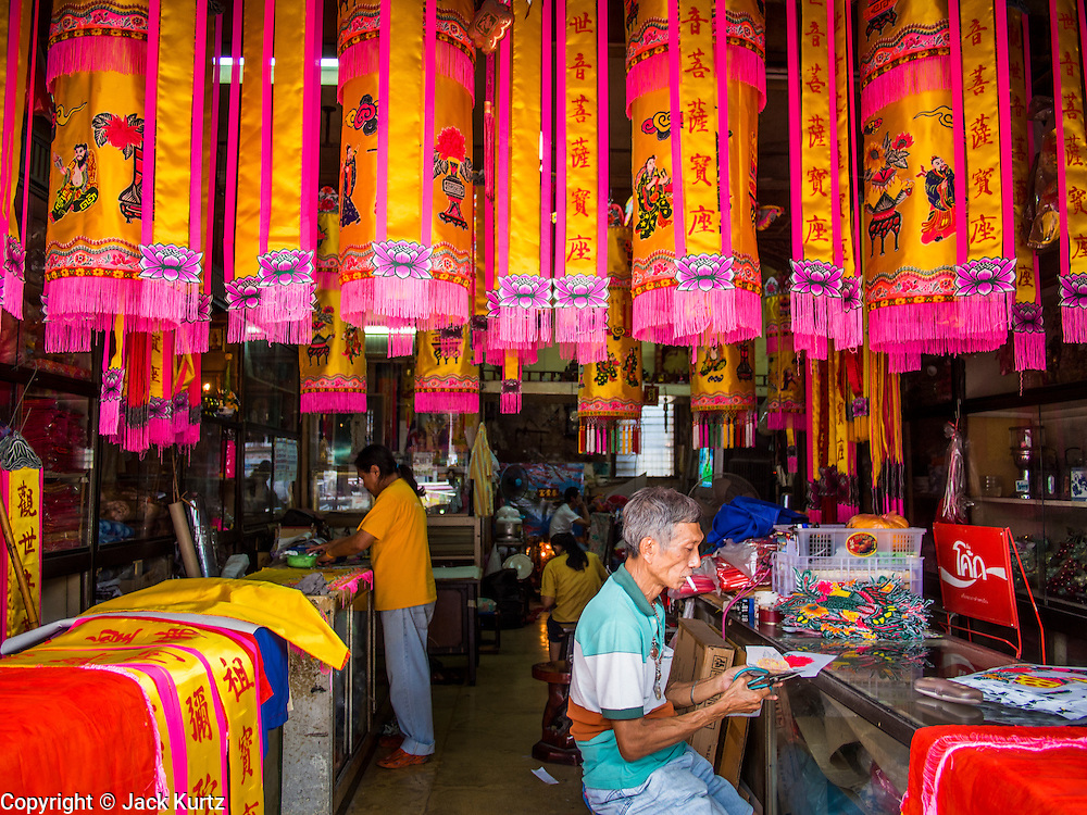 """26 AUGUST 2013 - BANGKOK, THAILAND: A shop worker in Bangkok's Chinatown makes decorations for the Hungry Ghost Month. The seventh lunar month (August - September in 2013) is when the Chinese community believes that hell's gate will open to allow spirits to roam freely in the human world for a month. Many households and temples will hold prayer ceremonies throughout the month-long Hungry Ghost Festival (Phor Thor) to appease the spirits. During the festival, believers will also worship the Tai Su Yeah (King of Hades) in the form of paper effigies which will be """"sent back"""" to hell after the effigies are burnt.      PHOTO BY JACK KURTZ"""
