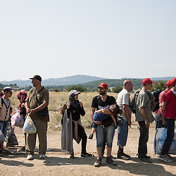 Shortly after crossing the border from Greece on August 26, 2015 refugees wait near a reception center in Macedonia. From here they will continue their journey north to other European states.