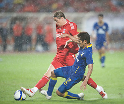 BANGKOK, THAILAND - Wednesday, July 22, 2009: Liverpool's Fernando Torres is brought down by a Thailand defender in Torres-ential rain during a preseason friendly match at the Rajamangala Stadium. (Pic by David Rawcliffe/Propaganda)