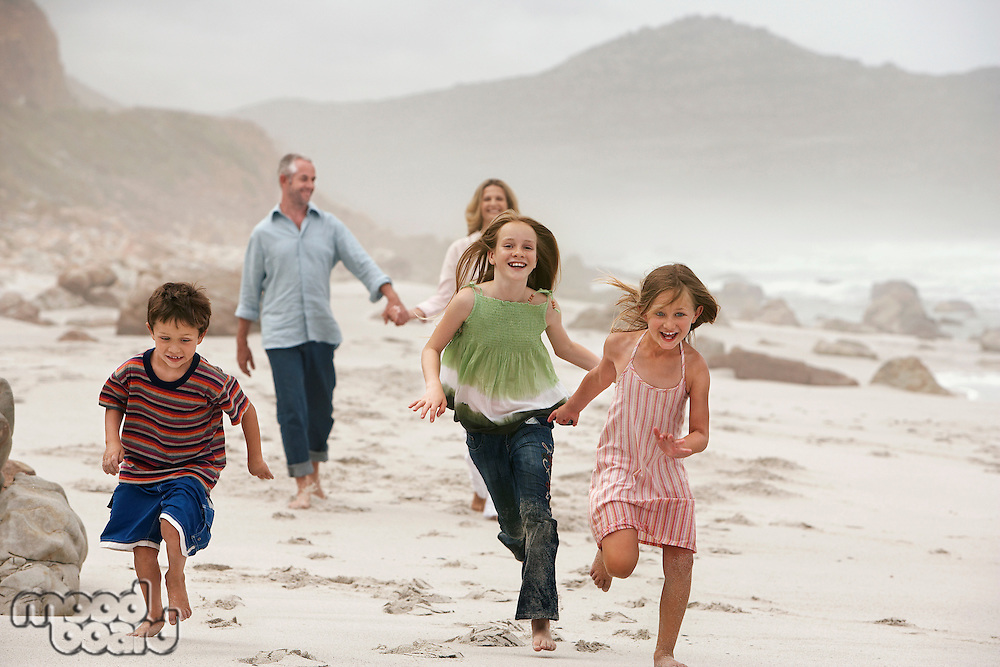 Family with three children (5-6 7-9 10-12) walking on beach