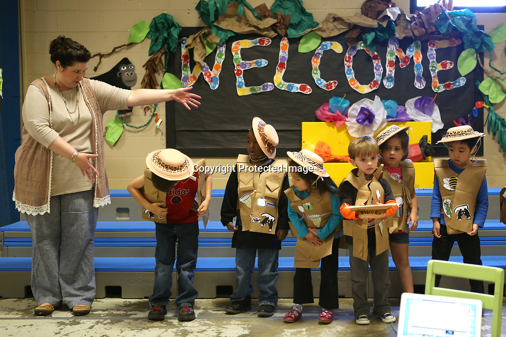 ECEC music teacher Aynsley Farmer, left, motions to the students to bow after their rehearsal for their Jungle Beats performance Monday morning at the school.