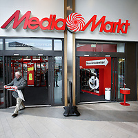 Nederland, Amsterdam , 25 februari 2011..Bezoeker verlaat met lege handen de Mediamarkt in amsterdam Noord..Client leaves electronics shop Mediamarkt without buying, just the deals folder.