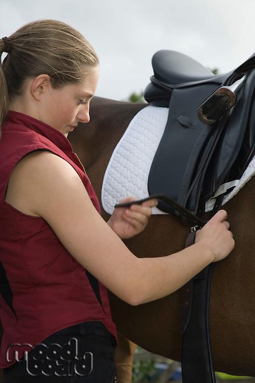 Girl tightening saddle on horse