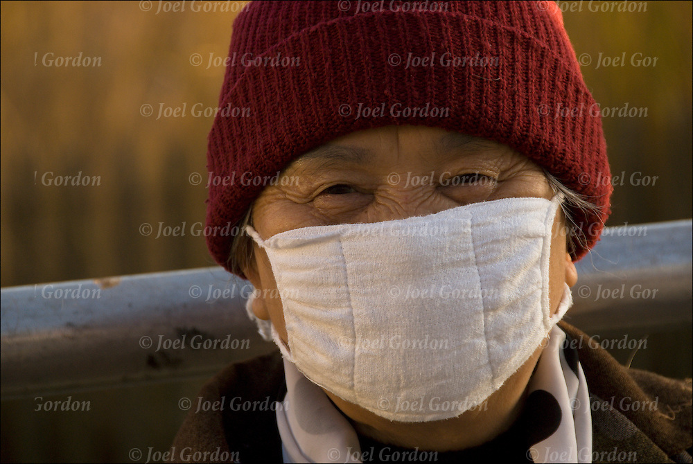 Head and shoulders portrait of elderly Asian woman in November on bench taking Swine Flu precaution, wearing surgical mask outdoors as a way to reduce the spread of illness.