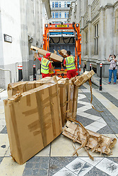 © Licensed to London News Pictures. 21/07/2019. LONDON, UK.  Workmen prepare to take away the broken pieces of The People's Tower, a monumental cardboard structure, built by artist Olivier Grossetête aided by a local volunteers, which stood in Guildhall Yard.  Over 1,000 boxes were used to build the 20m high artwork, inspired by the Guildhall building.  The four day construction process culminates in the structure being ceremonially torn down.  Photo credit: Stephen Chung/LNP