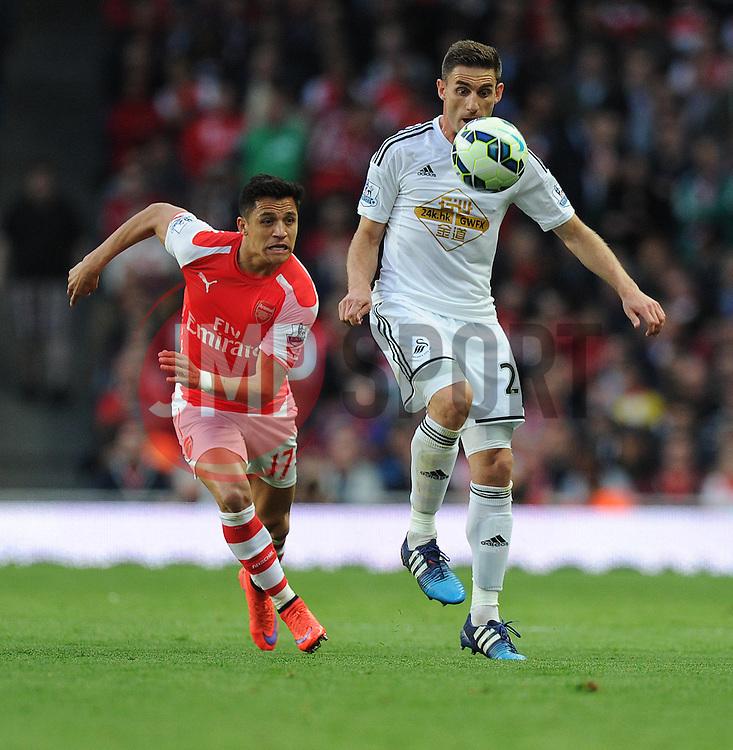 Swansea City's Angel Rangel controls the ball under pressure from Arsenal's Alexis Sanchez - Photo mandatory by-line: Alex James/JMP - Mobile: 07966 386802 - 11/05/2015 - SPORT - Football - London - Emirates Stadium - Arsenal v Swansea City - Barclays Premier League
