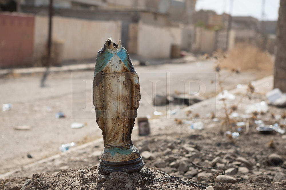 Licensed to London News Pictures. 23/10/2016. A statue of the Virgin Mary, with its head removed by Islamic State militants, is seen on a pile of rubble after being placed there by Iraqi soldiers in the town of Bartella, Iraq.<br /> <br /> Bartella, a mainly Christian town with a population of around 30,000 people before being taken by the Islamic State in August 2014, was captured two days ago by the Iraqi Army's Counter Terrorism force as part of the ongoing offensive to retake Mosul. Although ISIS militants were pushed back a large amount of improvised explosive devices are still being found in the town's buildings. Photo credit: Matt Cetti-Roberts/LNP