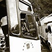 UN AYUDANTE DE AUTOBUS SILVA PARA LLAMAR AL CONDUCTOR, EN UNA PARADA PARA REPOSTAR <br /> COMBUSTIBLE. CARRETRA DE LOS YUNGAS . BOLIVIA <br /> FOTO : JORDI CAMI