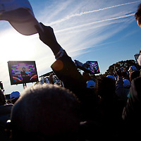 As images of Presidient Barack Obama appear on the screen, guests at wave their hats and cheer during the Martin Luther King Jr. Memorial Dedication Ceremony in Washington, DC, Oct. 16, 2010.