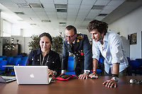 """PALERMO, ITALY - 6 JUNE 2016: (L-R) Reporter Rukmini Callimachi, Lieutenant Colonel Giuseppe Campobasso, Commander of the GOA unit (Gruppo Operativo Antidroga) and reporter Lorenzo Tondo are here in the conference room of the Guardia di FInanza (Financial Police) headquarters as they go over details of the seizures of vessels carrying hashish from Morocco to Libya, in Palermo, Italy, on June 6th 2016.<br /> <br /> Between January 2014 e December 2015 more than 120 tons of hashish, carried on fishing boats or cargo ships from Morocco to Libya, were seized in the Strait of Sicily by Italy's Guardia di Finanza (Financial Police) thanks to an international police investigation named """"Operazione Libeccio"""", carried out by the GICO (Gruppo Investigativo Criminalità Organizzata, Organised Crime Investigation Group), a unit of the tax police of Palermo under the supervision of the DDA (Direzione Distrettuale Antimafia) of Palermo.<br /> <br /> """"What is happening in Libya is same historical occurrence that happened years ago in Afghanistan. Such as the Talibans who financed their terroristic activities with heroin trafficking for the purchase of weapons, the Caliphate is proposing the same terroristic strategy by purchasing and commercialising hashish in order to purchase weapons used in their war"""" Sergio Barbera, Deputy General Prosecutor of Palermo, said."""