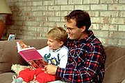 Father age 30 reading to son age 3 on living room sofa.   Burnsville Minnesota USA