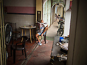 06 OCTOBER 2014 - GEORGE TOWN, PENANG, MALAYSIA: A Chinese Malaysian man reads a newspaper in a tea house in George Town (also Georgetown), the capital of the state of Penang in Malaysia. Named after Britain's King George III, George Town is located on the north-east corner of Penang Island. The inner city has a population of 720,202 and the metropolitan area known as George Town Conurbation which consists of Penang Island, Seberang Prai, Kulim and Sungai Petani has a combined population of 2,292,394, making it the second largest metropolitan area in Malaysia. The inner city of George Town is a UNESCO World Heritage Site and one of the most popular international tourist destinations in Malaysia.      PHOTO BY JACK KURTZ