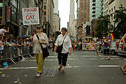 """Two women, one bearing a sign saying """"Proud to be a gay New Yorker,"""" marching in the 2011 Pride Parade on New York's Fifth Avenue."""