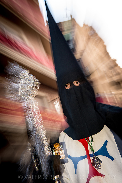 "La Trinidad Brotherhood in the evening of Holy Saturday walk in a central street in Sevilla. Here ""Nazarenos"", dressed with a black ""capirote"", the peculiar conical hat, and a white tunic  perform their penance carrying along the procession either long (and heavy) Paschal candles or wooden crosses."