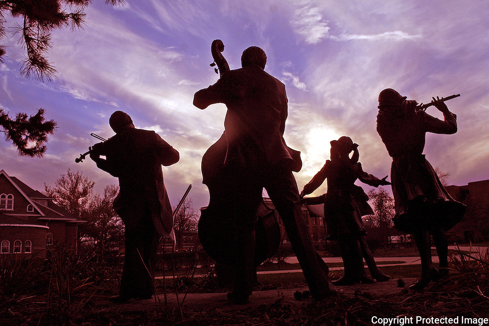 """""""The Joy of Music"""", a group of bronze sculpures, strike an elegant pose at dusk on the Drake University campus.  photo by david peterson"""