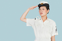 Beautiful young US Navy officer saluting over light blue background