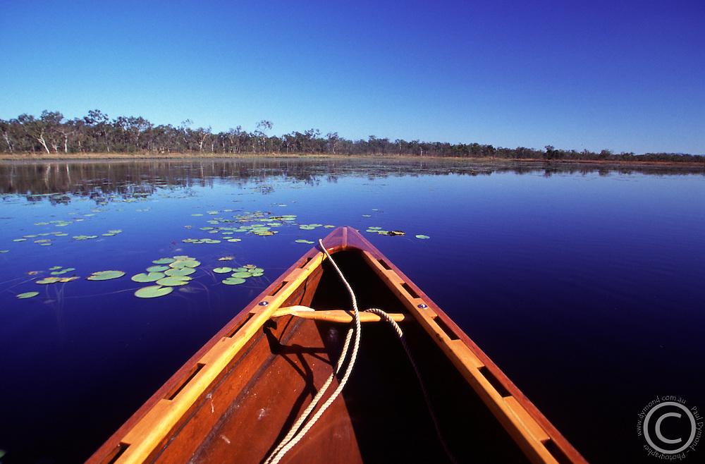 Paddling a wooden dugout canoe on Clancys Lagoon. Mareeba Wetlands, Mareeba, Queensland, Australia