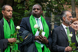 London, UK. 14th June, 2018. Faith leaders and politicians hold flowers outside St Helen's Church to mark the first anniversary of the Grenfell Tower Fire.