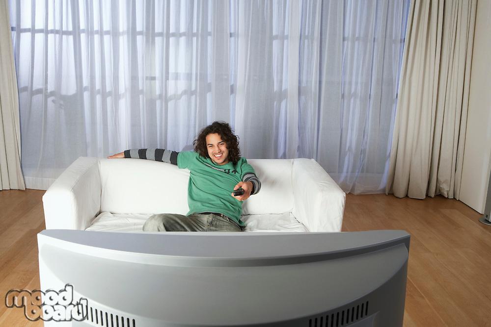 Man sitting on sofa watching television