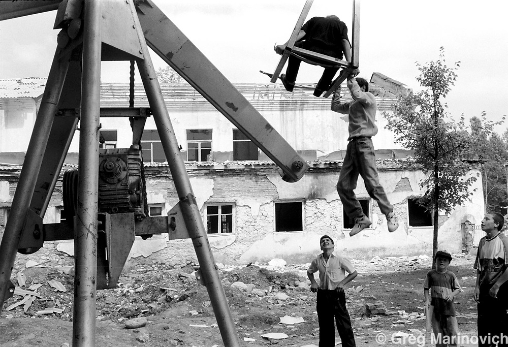 IPMG0843 Vedeno, Chechnya, 1995: Chechen children play in a damaged playground in the Russian occupied town of Vedeno, July 1995.  The town was occupied by Russian forces, but liberated soon after this image was taken.  Russia agreed to grant autonomy after Chechens retook several towns and the capital Grozny in 1995, after a bloody war for Chechen independence.  The Chechens are Moslem and have a strong sense of national identity.  Their fight for independence from Russia has increased an Islamic militancy and  identity. <br /> Photograph by Greg Marinovich