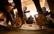 Children gather around a large plate of food during lunch at the Tangory Transgambienne 2 primary school in the town of Bignona, Senegal on Wednesday June 13, 2007.