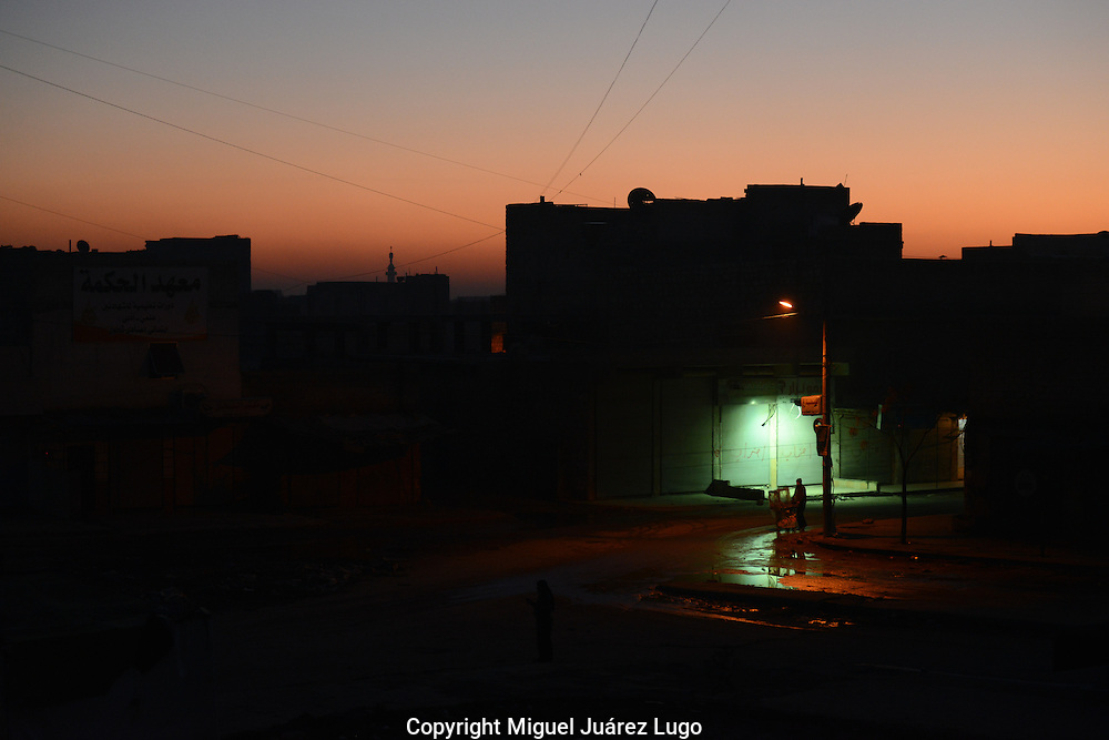 Aleppo, Syria, December, 2012.-  A street vendor offering harissa (a small sweet cake) passes underneath the only street lamp in several square miles of the Karam Jasmati neighborhood in this city. Many areas have been without power and water for more than 45 days. (Photo Miguel Juárez Lugo)