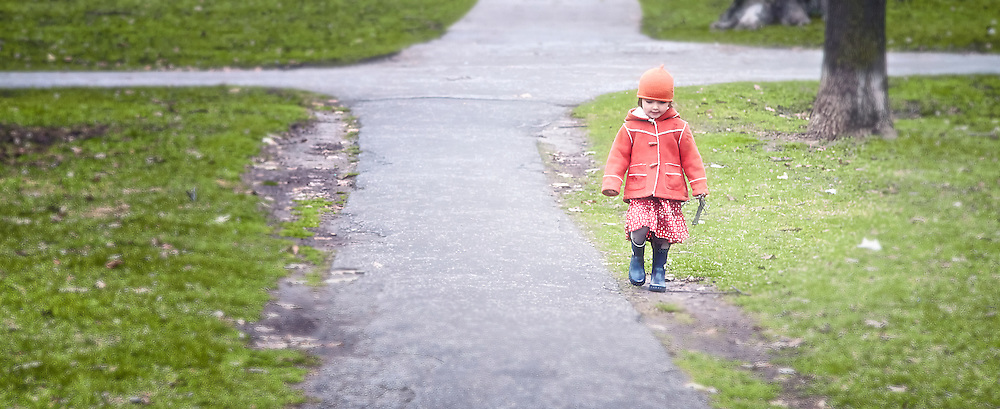 A little girl wearing a red hat and jacket walks down a paved path in a city park