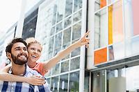 Cheerful woman showing something to man while enjoying piggyback ride in city