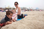 Seaside Heights, NJ - June 30, 2013 :  A family enjoys the beach in front of the newly restored boardwalk at Seaside Heights, NJ on June 30, 2013. People are returning to the beaches for the summer after recovery efforts post Sandy.