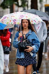 © Licensed to London News Pictures. 27/06/2017. London, UK. A woman with summer dress takes shelter from the rain under an umbrella on Whitehall in London on Tuesday, 27 June 2017. Photo credit: Tolga Akmen/LNP