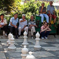 People watch and comment on the giant street chess game, Sarajevo, Bosnia & Herzegovina.