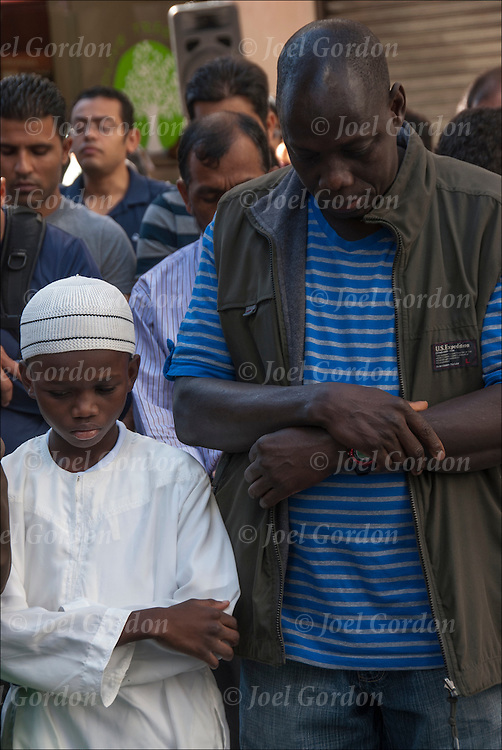 Gambia Muslim American father and son, wearing traditional white Muslim clothing, at the second of the five daily prayers, the Zuhur prayer or noon prayer before the start of the Muslim Day Parade in New York City.<br />